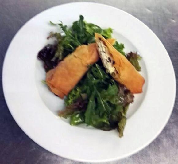 Mit Schafskäse gefüllte Teigtaschen an kleinem Salat